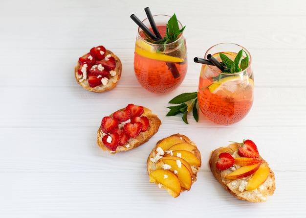 Coctails coloridos e brindes de frutas na mesa de madeira branca Foto Premium