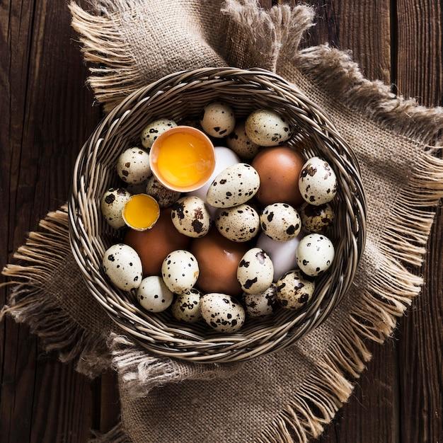 Codorna e ovos de galinha na cesta Foto gratuita