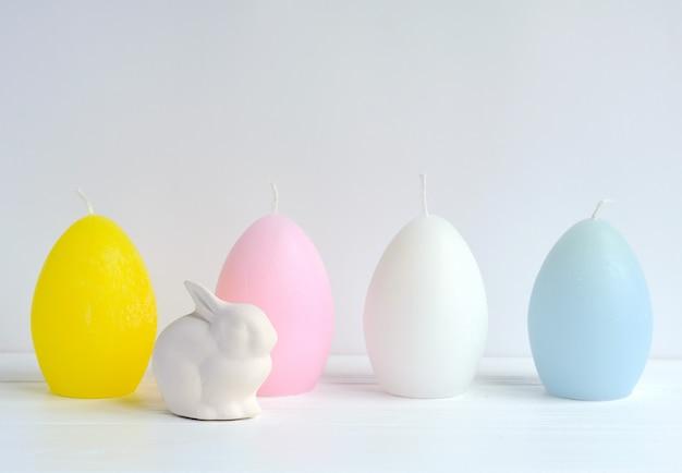 Coelhinho da páscoa com ovo em forma de velas em branco com copyspace Foto Premium