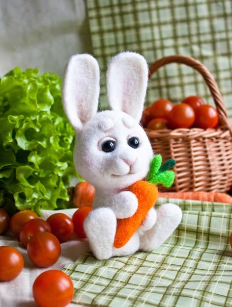 Coelhinho fofinho de feltro agulha com cenoura nas mãos no fundo de vegetais Foto Premium