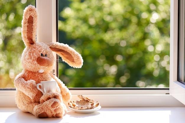 Coelho com uma xícara de café e biscoitos de manhã perto da janela aberta. bom dia e dia feliz. copie o espaço. Foto Premium