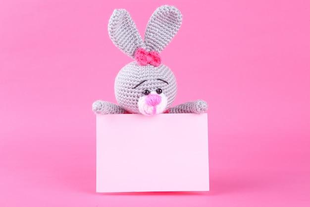 Coelho de malha no vestido rosa. decoração de são valentim. brinquedo de malha, amigurumi. cartão de dia dos namorados. Foto Premium