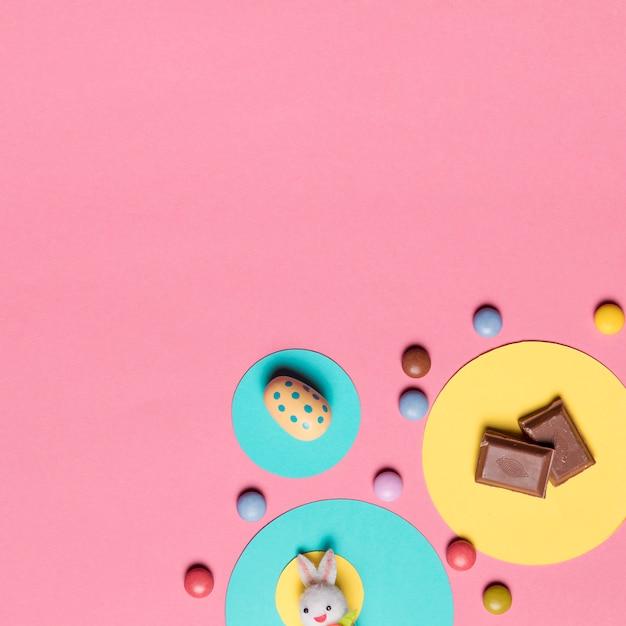 Coelho; ovos de páscoa; pedaços de chocolate e doces gema colorida no fundo rosa Foto gratuita