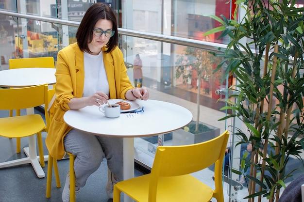 Coffee break. menina morena em uma jaqueta amarela com óculos Foto Premium