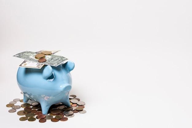 Cofrinho azul com dinheiro e moedas Foto gratuita