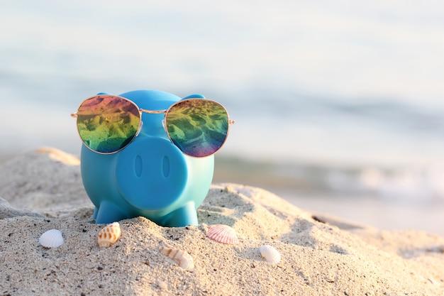 Cofrinho azul com óculos de sol na praia do mar, economizando o planejamento para orçamento de viagem do conceito de férias Foto Premium
