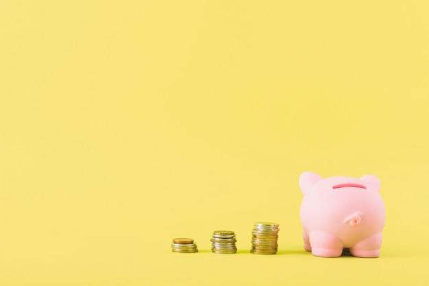 Cofrinho com colunas de moedas Foto gratuita