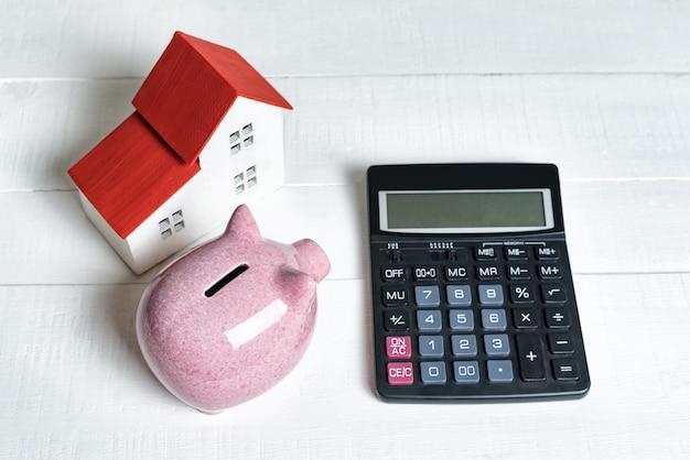 Cofrinho de porco rosa, calculadora e modelo de placa de ensaio de uma casa com um telhado vermelho sobre um fundo claro. conceito de aluguel, compra e venda de imóveis. Foto Premium