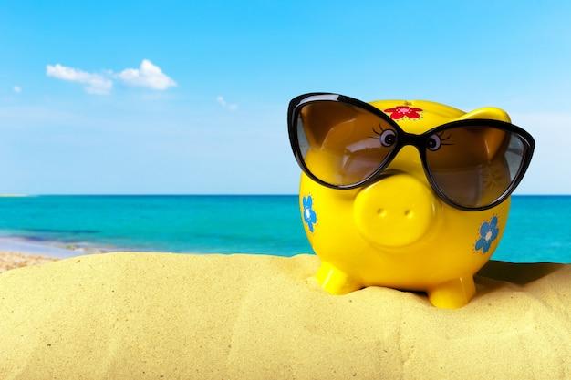 Cofrinho na praia. conceito de poupança de férias Foto Premium