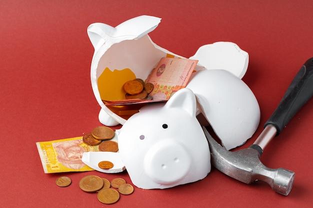 Cofrinho quebrado com notas e moedas de dinheiro ucraniano. declínio no conceito de padrões de vida Foto Premium