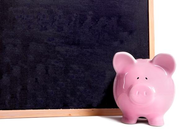 Cofrinho rosa ao lado de um quadro-negro Foto Premium