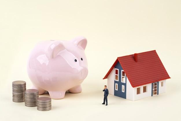 Cofrinho rosa e empresário em miniatura com casa modelo Foto Premium