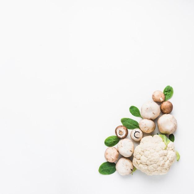 Cogumelos e espinafre perto de couve-flor Foto gratuita
