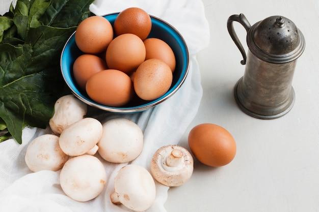 Cogumelos e ovos marrons de alto ângulo Foto gratuita