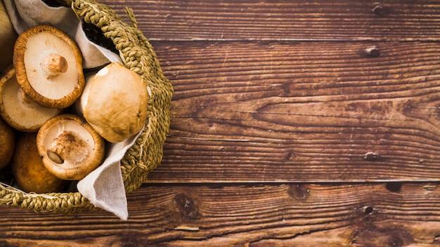 Cogumelos na cesta na mesa de madeira Foto gratuita