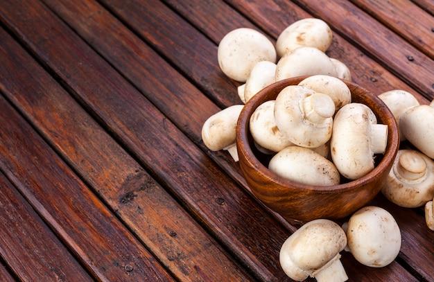 Cogumelos na tigela em madeira, copie o espaço. Foto Premium