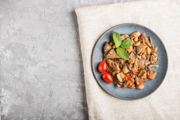 Cogumelos ostra fritos com tomate no fundo cinza de concreto Foto Premium