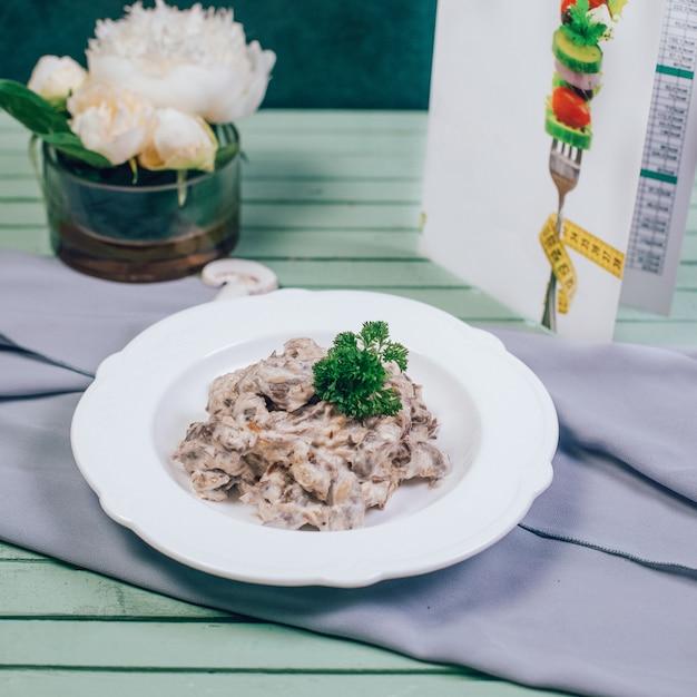 Cogumelos salteados com carne e ervas verdes. Foto gratuita