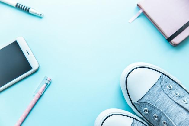 Coisas de adolescente hipster bloco de notas telefone tênis plana leigos sobre um fundo azul. conceito de volta às aulas. Foto Premium