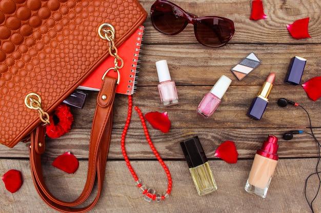 Coisas de bolsa de senhora aberta. bolsa das mulheres na madeira. imagem enfraquecida. Foto Premium