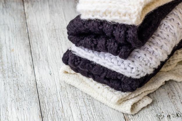 Coisas de malha dobradas brancas e pretas em um branco de madeira Foto Premium