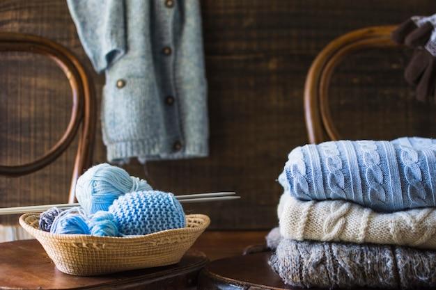 Coisas de tricô na cadeira perto de roupas Foto gratuita
