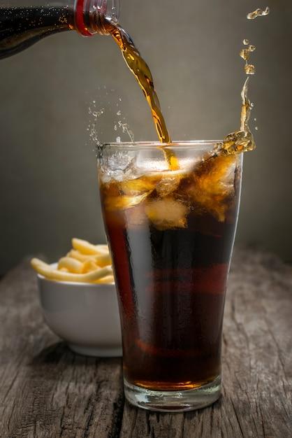 Cola de derramamento no vidro na tabela de madeira com fundo das batatas fritas. Foto Premium