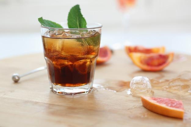 Cola de uísque cocktail com gelo em um copo. em uma placa de madeira são fragmentos de frutas. foto com profundidade de campo. Foto Premium