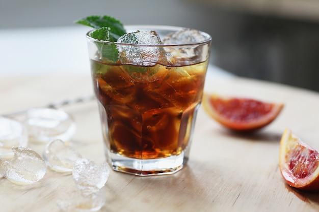 Cola de uísque cocktail com gelo em um copo. na placa de madeira são fragmentos de frutas. Foto Premium