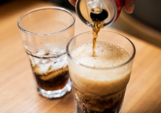 Cola fria derramada em um copo Foto Premium