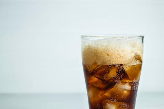 Cola, refrigerantes em um copo com fundo branco Foto Premium