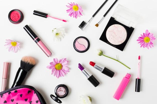 Colagem de cosméticos coloridos femininos na mesa branca Foto gratuita