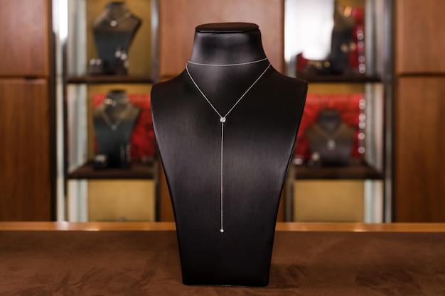 Colar de ouro branco com diamantes em um stand na boutique de joias de moda. suporte preto pescoço com jóias de luxo, acessórios femininos em vitrine. Foto Premium