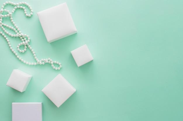 Colar de pérolas brancas com variedade de caixas brancas sobre fundo de papel verde pálido Foto gratuita