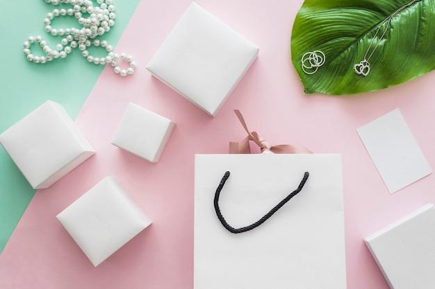 Colar de pérolas e muitas caixas brancas com saco de compras em pano de fundo rosa Foto gratuita
