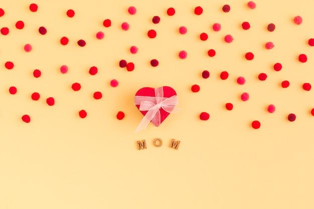 Coleção de coração decorativa e confetes perto do título da mãe Foto gratuita