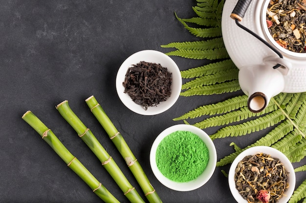 Coleção de ingrediente de chá seco aromático na superfície preta Foto gratuita