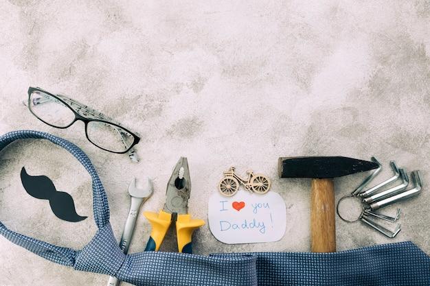 Coleção de instrumentos perto de bigode decorativo com eu te amo papai palavras e gravata Foto gratuita