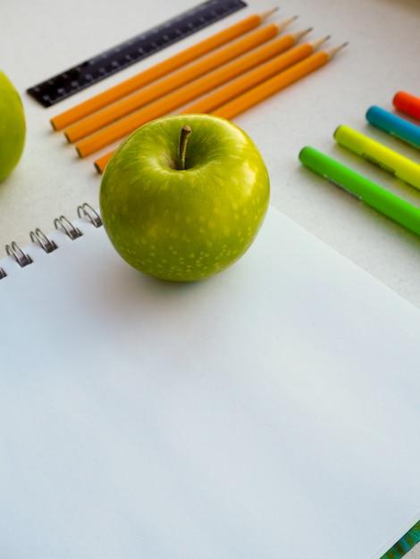 Coleção de material escolar colorido no notebook Foto Premium
