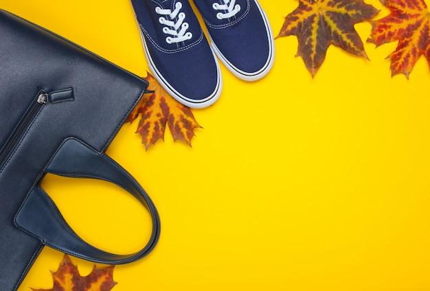 Coleção de outono. bolsa de couro, sapatos de pano, folhas caídas de outono em amarelo. acessórios sazonais. vista do topo. copie o espaço Foto Premium