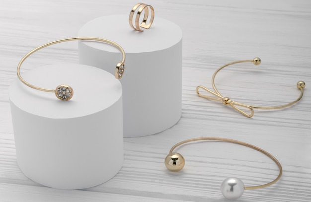 Coleção de pulseiras modernas douradas e anel em plataformas brancas sobre fundo de madeira Foto Premium