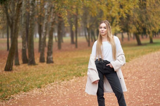 Coleção de rua moderna. jovem loira confiante, vestindo camisa branca, calça jeans preta e casaco de outono na moda Foto Premium