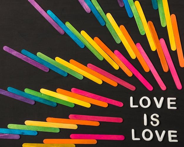 Coleção de varas em cores brilhantes lgbt e amor é palavras de amor Foto gratuita