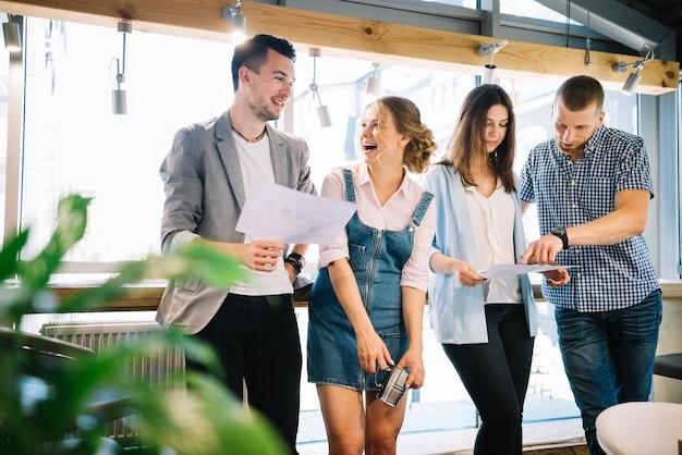 Colegas alegres discutindo planos de trabalho durante a pausa Foto gratuita