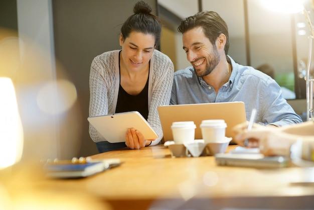 Colegas atraentes compartilhando idéias de negócios no espaço de trabalho de co Foto Premium