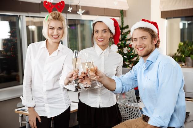Colegas, comemorando a festa de natal no escritório, bebendo champanhe sorrindo. Foto gratuita