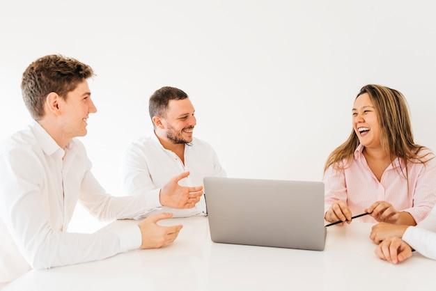 Colegas de brainstorming e rindo no escritório Foto gratuita