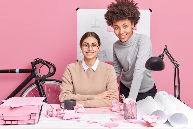 Colegas de mulheres felizes, preparadas para a sessão de trabalho, têm expressões alegres pose na área de trabalho estando de bom humor pose na mesa do escritório rodeado por desenhos de projetos de papéis. conceito de trabalho em equipe Foto gratuita