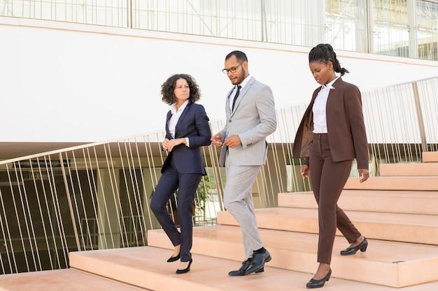 Colegas de negócios sérios caminhando juntos para seu escritório Foto gratuita