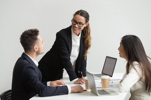 Colegas de trabalho analisando apostilas e relatórios durante a reunião Foto gratuita